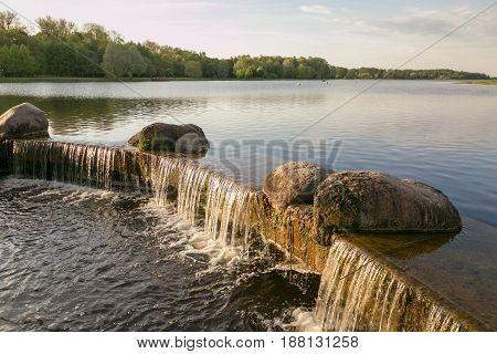 Waterfall on the lake in the spring evening.