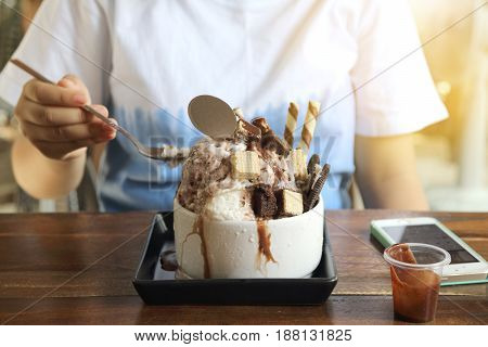 Little girls are eating Bingsu Vanilla ice cream with brownie chocolate chip and chocolate sauce