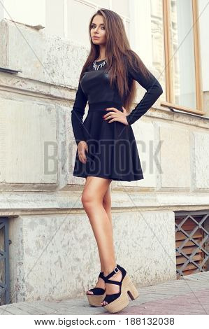 full length portrait of young beautiful sexy stylish girl wearing black dress and black shoes posing at city street against house wall