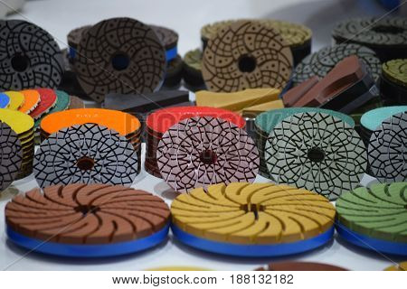Grinding discs in various shapes and colours, neatly arranged in line