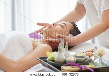 Female beauty therapist preparing skin of her pretty client before applying facial mask, side view