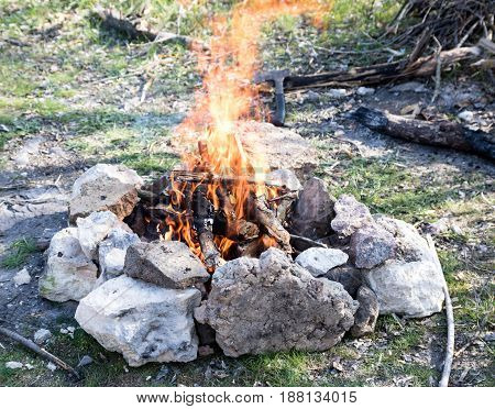 Fireplace Made From Stones, Campfire, Firewood, Big Flame, Axe On The Background