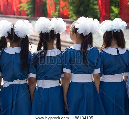 Choir of girls with white bows on head .