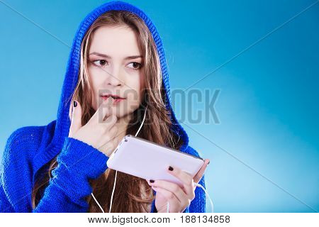 young woman with smart phone listening music. Teen stylish long hair girl in hood relaxing or learning language. Studio shot on blue.