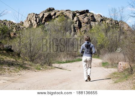 Female Hiker Is Walking To The Rocks. White Road, Bushes And Trees, Springtime