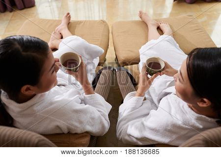 High angle view of two pretty friends drinking herbal tea and chatting animatedly while relaxing in spa salon