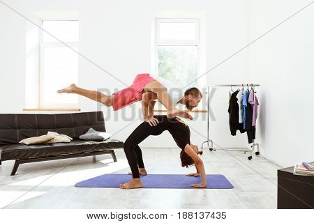 Young beautiful sportive couple stretching, practicing yoga asanas at home. Copy space.