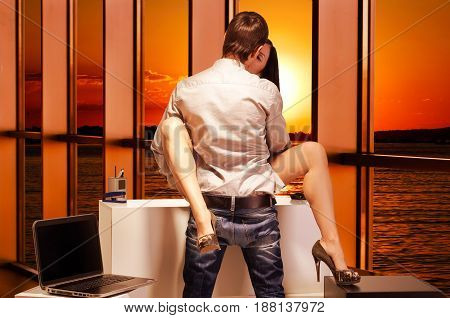 Beautiful young couple having sex in the office at sunset