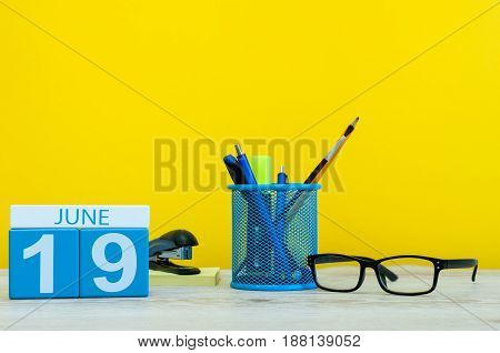 June 19th. Day 19 of month, calendar on yellow background with office suplies. Summer time at work.