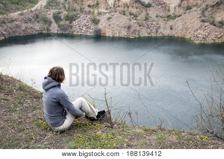Girl Sits On The Big Stone Abobe The Blue Lake. Rocky Screes On The Banks. Hugs Her Legs
