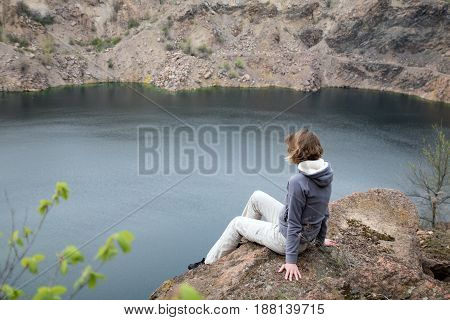 Female Sits On The Edge Of The Cliff Abobe The Blue Lake. Rocky Screes On The Banks. Close-up