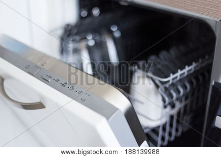 Close Up Of Open Dishwasher With Clean Utensils