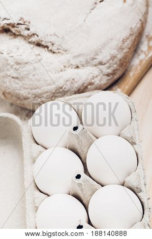 Fresh baked bread, flour and eggs on a wooden table. soft light