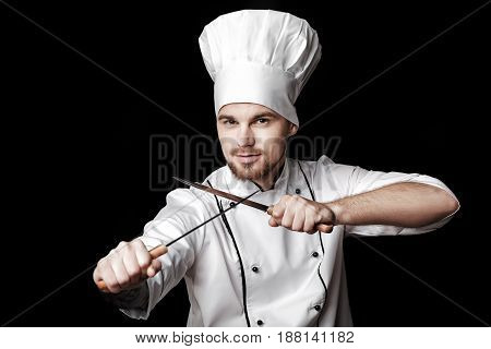 Young bearded chef in white uniform holding two knives on a black background