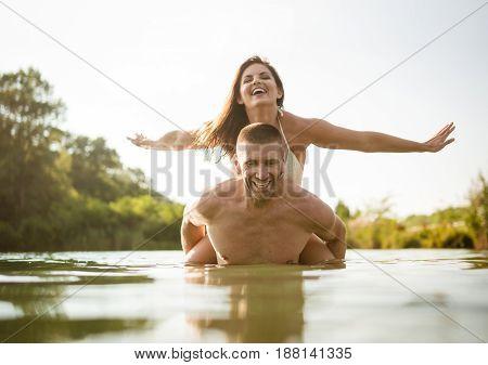 Playful romantic couple having fun as the woman enjoys a piggy ride