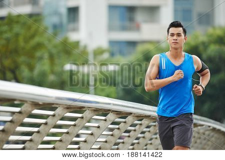 Daily routine of Asian sporty man: he running on city bridge road and listening to music in headphones