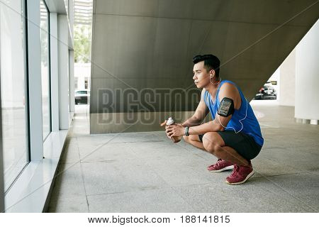 Concentrated Vietnamese sportsman with armband and fitness tracker drinking water while sitting on haunches after intensive training poster