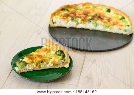 Traditional French quiche Lorraine with chicken, egg, milk, cheese broccoli and corn on a wooden background.