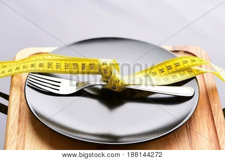 Fork Tied With Twisted Yellow Measuring Tape Lying On Plate