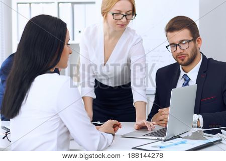 Business people at a meeting in the office. Focus on woman pointing into laptop.