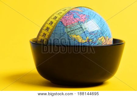 diet and healthy lifestyle in world concept measuring tape and globe in bowl on yellow background