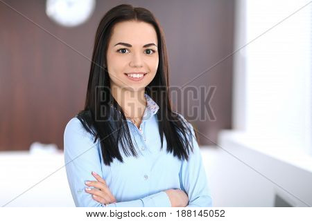 Young business woman or student-girl standing with crossed arms  in office. Blue colored blouse. Education or business concept.
