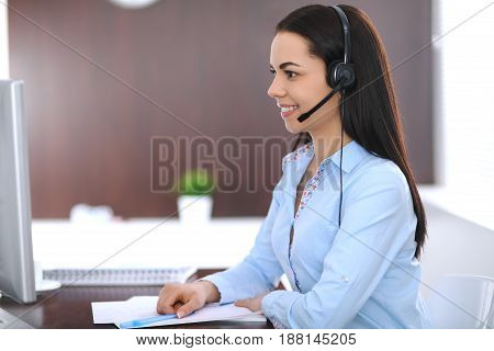Young business woman or student girl with headset in office. Call center or support staff concept