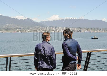 May 28 2017- Two man standing,talking and seeing a nice view of Canada Place at Vancouver,BC Canada