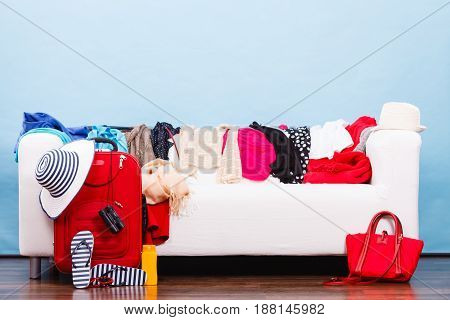 What to wear packing for travel concept. Messy colorful clothing lying on white sofa