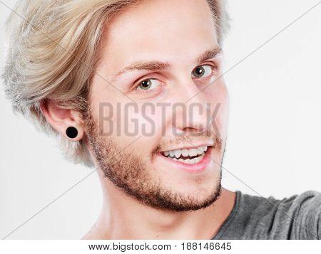 Fashion happiness joy concept. Happy smiling blonde man wearing grey t shirt studio shot close up grey background