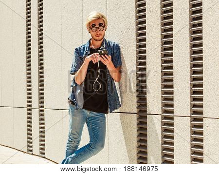 Men fashion technology urban style clothing concept. Hipster guy standing on city street wearing jeans outfit and weird sunglasses listening to music and looking at phone