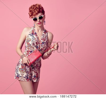 Fashion Redhead Model in Sexy Jumpsuit, woman in Trendy Summer Dress. Stylish Curly hairstyle, fashion Sunglasses, Summer Floral Outfit.Glamour fashion pose.Playful Beauty Girl, Luxury Pink Clutch