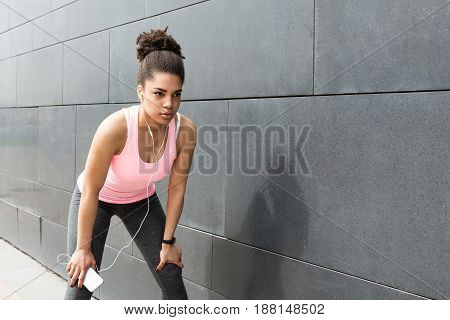 Young woman resting after exercising, standing at wall