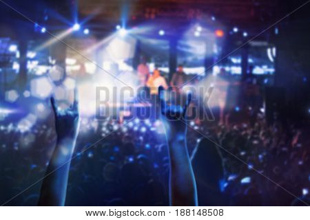 The silhouettes of concert crowd in front of bright stage lights. Concert of an abstract rock band