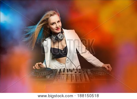 Beautiful blonde DJ girl in a white suit on decks on the party on the black background