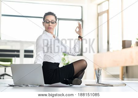 Concentrated woman demonstrating relaxation while working with notebook computer in room