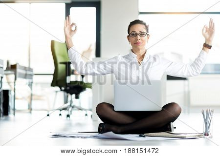 Happy secretary demonstrating tranquility while working with notebook computer. She sitting on floor and keeping it on legs. Yoga concept. Portrait