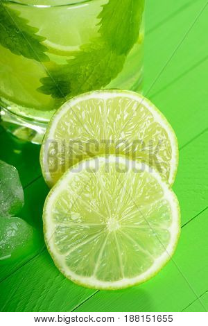 A Glass Of Mojito With Ice, Limes And Mint On Wooden Boards