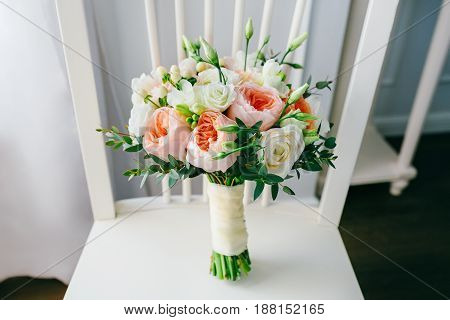 Wedding bouquet of flowers on the white wooden chair. close-up. Indoors.