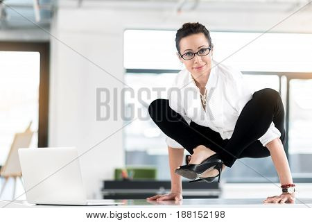 Portrait of secretary expressing gladness while locating in awkward pose on table in office. Business concept