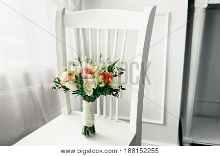 Bridal bouquet on the white wooden chair. close-up. Indoors.
