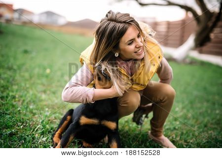 Adorable Woman Playing And Hugging Her Puppy On A Late Afternoon