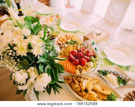 The above view of the fruit and different dishes placed on the wedding table near ther huge white bouquet