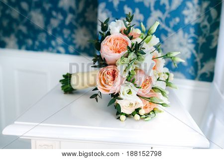 bridal bouquet of different flowers wrapped ribbon near the blue white vintage wal on the white wooden floor