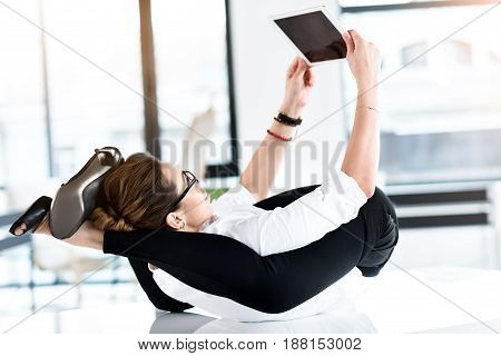 Side view flexible smiling female looking at electronic tablet while lying on back at work in bright room