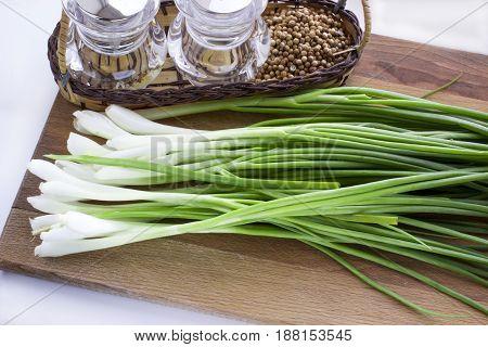 Green onion on a cutting board .