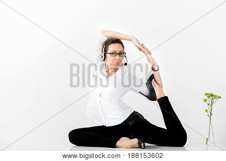 Portrait of smiling female making yoga during work wearing earphones. Copy space
