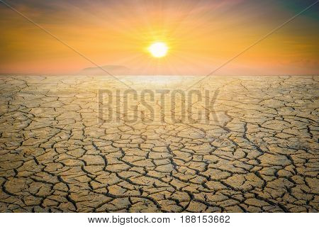 Dry cracked soil dirt or earth during drought at sunset.