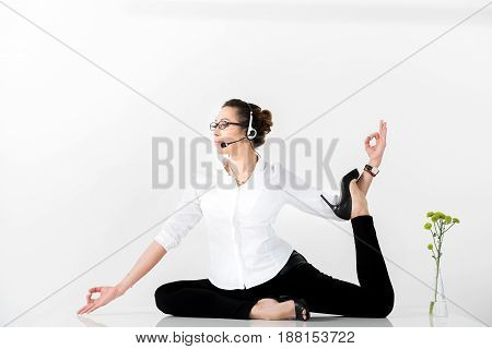 You should always be in good form. Side view happy operator speaking by earphones while doing gymnastics. Copy space