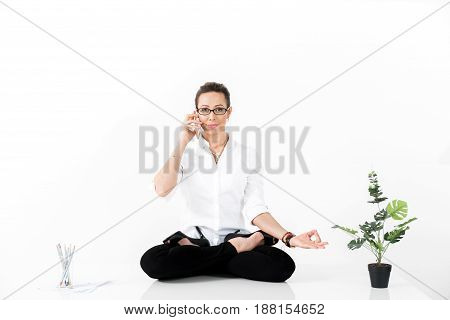 Portrait of smiling female meditating while speaking at mobile. She sitting in lotus pose. Copy space. Relaxation concept